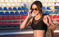 Young Beautiful Woman Talking On Cell Phone At The Stadium. Athletic Fashion Girl In Sunglasses At The Stadium. Stock Images - 77900254