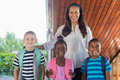 Portrait Of Smiling Teacher And Kids Standing Together With Arm Around Stock Photos - 77909933