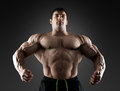 Handsome Muscular Bodybuilder Posing Over Black Background. Stock Photo - 77924560