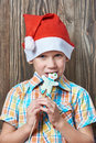Little Boy In New Year S Red Cap Eats Christmas Cookies Royalty Free Stock Photo - 77926965
