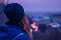 Hipster Girl Traveler Looking At Winter Evening Cityscape, Violet Sky And Blurred City Lights Royalty Free Stock Photo - 78019525