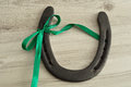 A Horse Shoe Tied With A Green Ribbon Stock Photo - 78022020