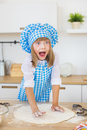 Pretty Little Girl In A Cook Clothes Sculpts A Dough And Open Your Eyes And Mouth On A Kitchen Royalty Free Stock Images - 78044259