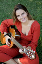 Casual Girl Dressed In Red Playing Guitar Royalty Free Stock Photo - 78114465