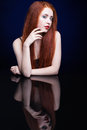 Young Woman With Ginger Hair Over Reflection Mirror On Blue Back Stock Photo - 78197440