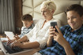 Woman Working On Her Laptop And Two Boys Playing Tablet And Smart Phone Stock Photos - 78246973