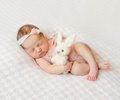 Sleeping Newborn Girl With Headband And Holding Toy Stock Images - 78248434