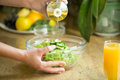 Hands Pouring Oil In A Green Salad Stock Images - 78491284