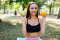 Young Slim Woman Having Snack After Working Out Outdoors In The Park. Sitting On The Grass, Eating Juicy Apple On Fresh Air Royalty Free Stock Images - 78536419