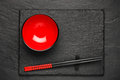 Two Chopsticks And Red Plate On Black Stone Background With Copyspace Royalty Free Stock Image - 78537016