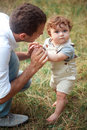 Young Beautiful Father And Little Toddler Son Against Green Grass Royalty Free Stock Photography - 78605737