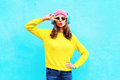 Fashion Pretty Cool Girl In Headphones Listening To Music Wearing A Colorful Pink Hat Yellow Sunglasses And Sweater Over Blue Stock Photography - 78645082