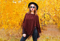 Fashion Pretty Woman Model Wearing A Black Hat, Sunglasses And Knitted Poncho Over Autumn Yellow Leaves Stock Image - 78645291