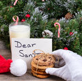 Santa Claus Hand Reaching For A Cookie With Holiday Decorations Stock Photos - 78648053
