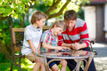 Two Little Kid Boys And Father Playing Together Checkers Game Stock Image - 78660901
