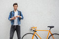 The Guy In A Blue Denim Jacket Standing On Wall Background.  Young Man Near Orange Bicycle. Smiling Student With Bag Royalty Free Stock Photo - 78674575
