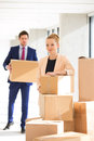 Portrait Of Confident Young Businesswoman Standing By Stacked Boxes With Male Colleague In Background At Office Royalty Free Stock Photos - 78724078