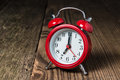 Red Alarm Clock On The Wooden Table Stock Image - 78746601