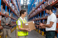 Female Worker Holding Cardboard Box While Male Worker Scanning Barcode Stock Image - 78920751