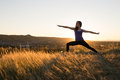Woman Doing Yoga Warrior II Pose During Sunset Royalty Free Stock Photos - 79074338