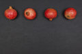Whole Ripe Pomegranates In A Row On Dark Grey Background Stock Photography - 79094752