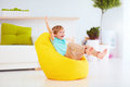 Excited Kid Having Fun, Sitting On Yellow Bean Bag At Home Royalty Free Stock Image - 79132996