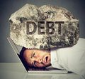 Man Squeezed Between Laptop And Rock. Student Loan Debt Concept Stock Image - 79135291
