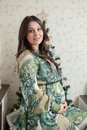Happy Young Pregnant Woman Sitting Near The Christmas Tree Stock Photo - 79236460