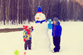 Little Boy And Girl Play With Snowman In Winter Nature Royalty Free Stock Photos - 79529068