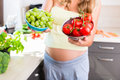 Pregnant Woman Showing Fruit And Vegetables Stock Images - 79599744