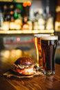 Hamburger And Dark Light Beer On A Pub Background. Royalty Free Stock Photos - 79680208