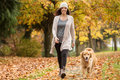 Happy Woman Walking Her Golden Retriever Dog In A Park With Fall Stock Image - 79702631