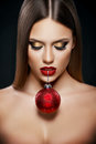 Beautiful Woman Holding A Christmas Ornament With Teeth Over Dark Background Stock Image - 79730831