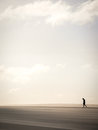 Solitary Man Walking Through Sand Dunes Stock Photography - 79795542