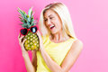 Happy Young Woman Holding A Pineapple Royalty Free Stock Photography - 79807407