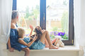 Two Cute European Toddler Girls Sitting On Sill Near Window Royalty Free Stock Photography - 79983327