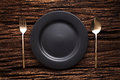 Black Empty Plate Fork Spoon On Wooden Table Background Stock Photo - 79997370