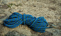 Blue Climbing Rope Laying Folded On A Rock Stock Photo - 80022310