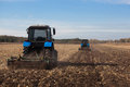 The Sloping Field. Two Large Blue Traktor Plow Plowed Land After Harvesting The Maize Crop Royalty Free Stock Photography - 80151017