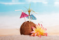 Coconut With Straw Umbrellas And Flower In Sand Against Sea. Royalty Free Stock Photos - 80199478