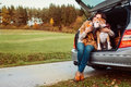 Woman With Dog Sits In Car Trunk On Autumn Road Stock Photo - 80223440
