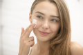 Young Smiling Woman Applying Cream To Face In The Bathroom Stock Photography - 80256372