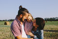 Father And Mother Hug Their Little Daughter Outdoors In Field Royalty Free Stock Photos - 80322338