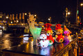 New Year`s Toys Snowmen And Deer Pose Against Night Canals Of Amsterdam. Stock Image - 80329271