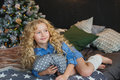 Portrait Of Blonde Little Girl In Blue Dress Lies And Looks Side On A Bed In Christmas Dark Room Stock Photo - 80332490