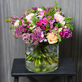 Bouquet With Cream Roses And Purple Flowers In A Glass Vase Stock Photo - 80375420