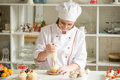 Portrait Of Confectioner Topping A Cupcake With Cream Royalty Free Stock Photography - 80375747