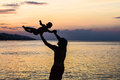 Young Happy Father Holding Up In His Arms Little Son Putting Him Up At The Beach In Barefoot Standing In Front Of Sea Waves Wet Sa Stock Image - 80482571