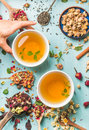 Two Cups Of Healthy Herbal Tea With Mint, Cinnamon, Dried Rose And Camomile Flowers In Different Spoons, Woman`s Hand Stock Photo - 80580520