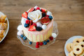 Cake With Various Berries, Meringues And Rose On Cakestand. Royalty Free Stock Image - 80693326
